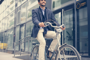 Smiley businessman driving bike on street.