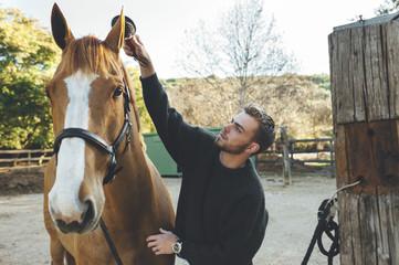Horse man brushing horse manes outside stable at sunrise