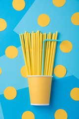 Yellow and blue straws for a party in paper cups on a bright background