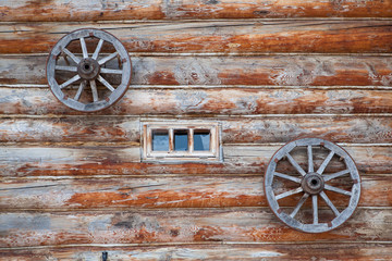 Old farm house wooden wall and wagon wheels