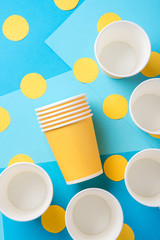 Yellow paper cups for a party on a blue background