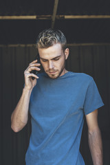 Portrait of handsome attractive millennial man talking by phone in the door of a barn