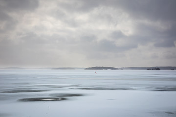 Beautiful winter seacape with hazy clouds and frozen sea.