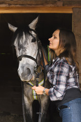 girl in plaid shirt with a horse in a stable