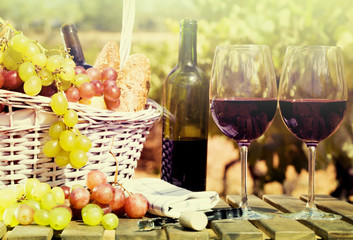 red wine ripe grapes and picnic basket on table in vineyard