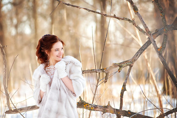 The bride in a white fur coat looks away and smiles among the branches of trees on a winter sunny day. Wedding hairstyle and makeup.