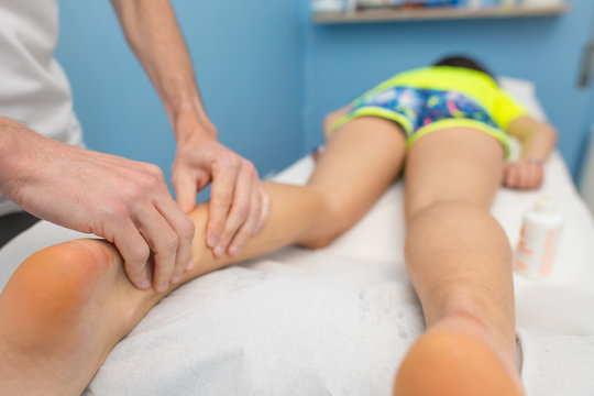 Physiotherapist performs Achilles tendon treatment.