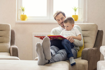 Father and son reading book and having fun while spending time together at home