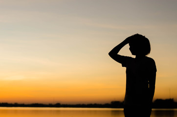 The silhouette of a woman standing looking forward with hope.