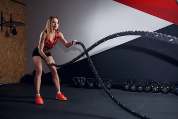 Portrait of female athlete in training with two black ropes
