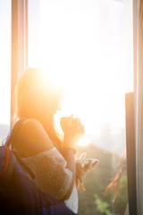 Photo of long-haired pensive woman with cup of tea and backpack by window in room.