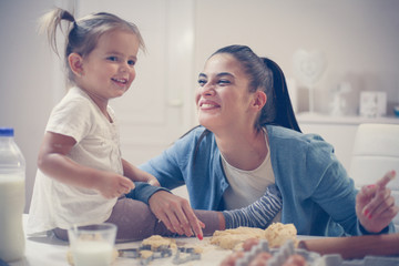 Cheerful mother and little girl baking cookie in kitchen.