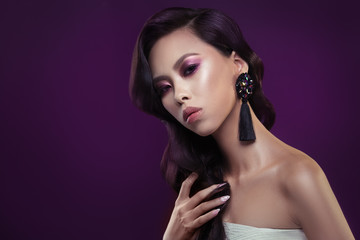 Fashion beauty portrait of a chic girl of Asian appearance with an elegant wave arrangement on a purple background.