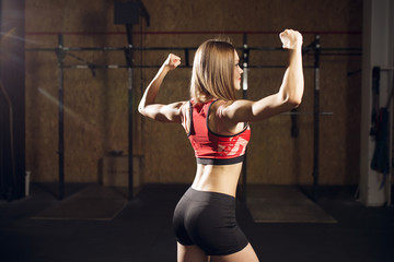 Portrait from back of sports woman showing biceps