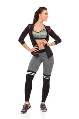 Beautiful Young Woman In Sports Clothes Is Standing With Hand On Hip And Looking Away. Front View.