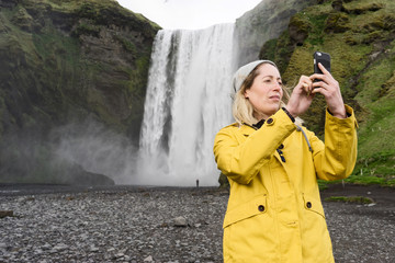 Woman taking a picture on mobile phone with a waterfall behind her