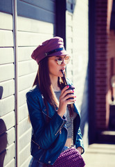 Portrait of smiling girl in sunglasses drinking coffee to go.