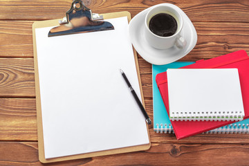 Office desk table top view. Notepad with blank pages on wooden table