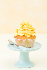 Cupcake with yellow cream decoration on blue stand on yellow background - pastel vertical banner. Minimalism still life concept.