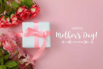 Top view aerial image of decoration Happy mothers day holiday background concept.Flat lay white gift box with red rose on modern beautiful pink paper at home office desk.Free space for design text.