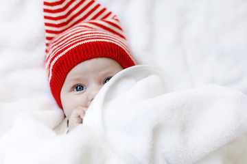 Cute adorable baby child with Christmas winter cap on white background