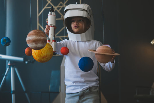 Cute little boy wearing cardboard astronaut helmet flying toy rocket through planets, cardboard spaceship rocket in the background