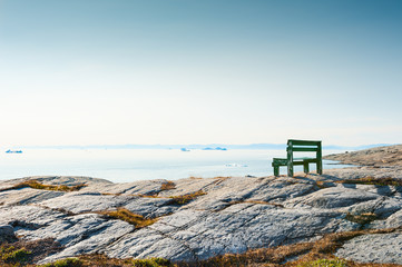 Lonely bench on the rocky coast in Greenland