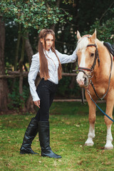 portrait beautiful young girl in white shirt and black pants with beauty long hair next horse in forest. Fashionable elegance woman posing near animal. Beauty Lifestyle Fashion People Animals concepts
