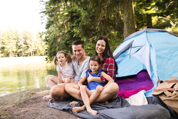 Spoed Foto op Canvas Kamperen Beautiful young family with daughters camping in forest.