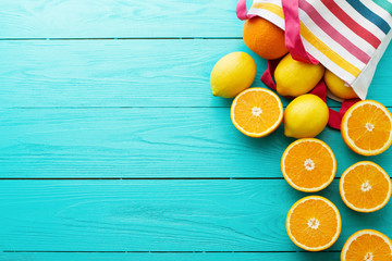 Summer fun time. Fruits on blue wooden background. Mock up and picturesque. Orange, lemon fruit in bag on table. Top view and mock up. Copy space