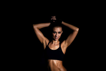 Smiling fit woman posing and looking at camera. Black background.