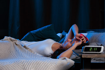 Picture of young woman with insomnia lying on bed next to clock