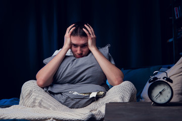 Photo of man with insomnia with pillow sitting next to alarm