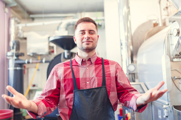 Picture of happy barista man in apron on background of industrial coffee grinder