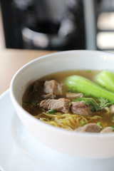 Chinese noodles with pork on wood background