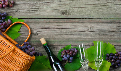 Wine bottles with grapes, basket, two wineglasses on wooden background. Top view