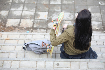 A young hipster girl is riding a skateboard.