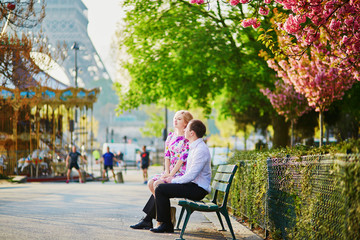 Couple in front of the Eiffel tower on a spring day in Paris, France