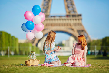 Two young women having picnic near the Eiffel tower in Paris, France