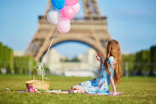 Woman in pink dress with bunch of balloons having picnic near the Eiffel tower in Paris