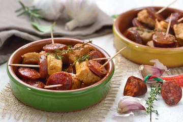 Spanische Pinchos: Geschmorte Schweinefilet-Stückchen mit angebratener scharfer Chorizo Paprikasalami serviert – Spanish snack: Braised pork fillet with fried slices of chorizo paprika sausage