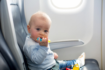 Cute baby boy, playing with toys on board of aircraft, traveling with parents and siblings