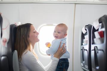 Young mom, playing and breastfeeding her toddler boy on board of aircraft