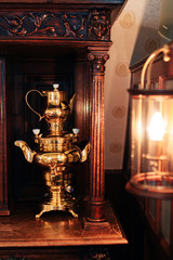 Vintage samovar and wall lamp in dark tones
