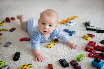 Adorable baby boy, lying on the floor, toy cars around him