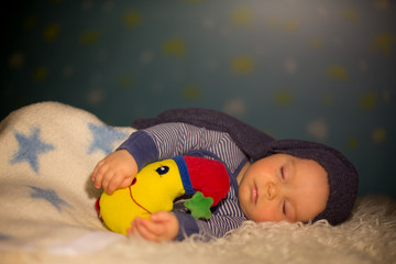 Little baby boy with cute teddy bear and moon on a blue star and moon background