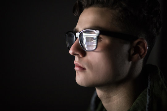Close up of man face. Eyes of serious young man in black rim glasses using his tablet computer. Screen and finger reflecting in the glass