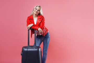 Young beautiful blonde woman with suitcase on pink background.
