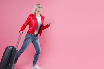 Happy young woman with travel suitcase with mobile phones. Blonde tourist girl on pink background, call a taxi