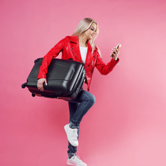 Use Navigator in smartphone, concept on pink background. Young woman with suitcase under her arm